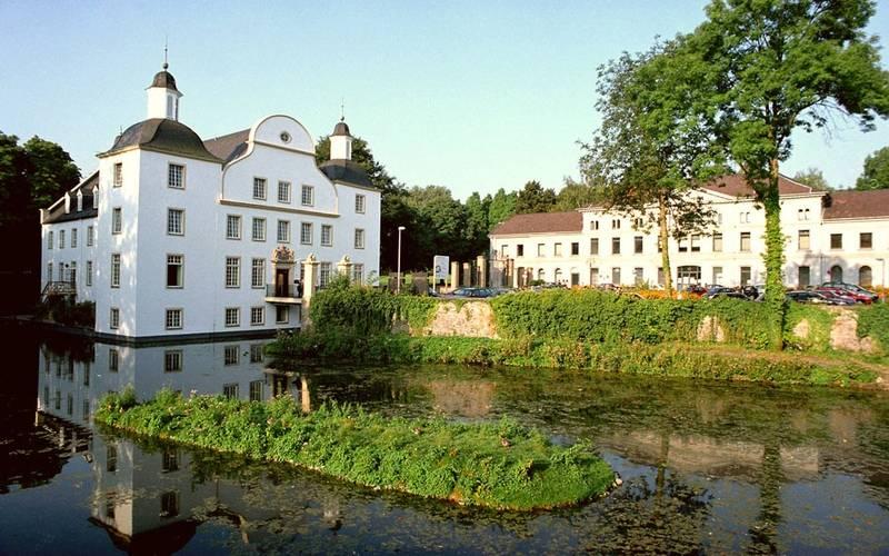 Das Schloss Borbeck ist ein weißes großes Schloss mit hohen Fenstern, direkt an einem kleinen See gelegen mit einem Park dahinter.