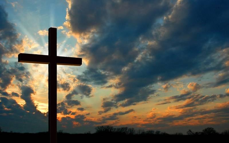 Kreuz steht vor Himmel mit Sonnenstrahlen durch Wolken